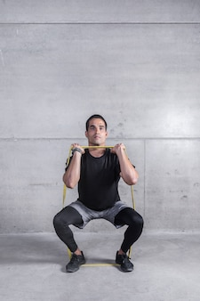 Focused personal trainer doing exercise with elastic band