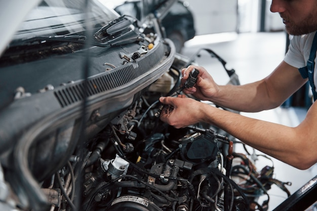 Focused photo. employee in the blue colored uniform works in the automobile salon.