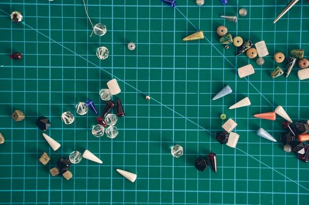 Сфокусированные фото стеклянных и бисерных бусин и войлочных бусин для изготовления ювелирных изделий, изолированные на зеленом фоне