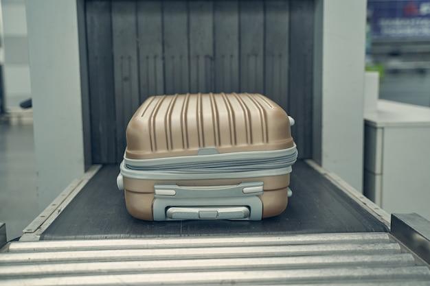 Сфокусированное фото багажа на магнитной ленте во время подготовки к посадке в самолет