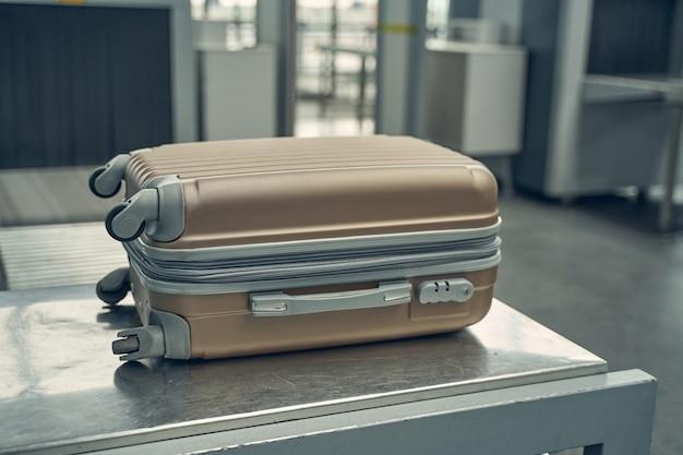 Сфокусированное фото багажа, лежащего на металлической опоре на стойке регистрации перед переходом в самолет.