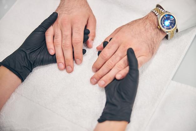 Сосредоточенное фото на стильных часах на мужской руке, добрый мужчина делает маникюр
