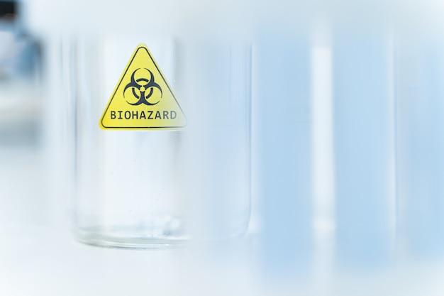 초점을 맞춘 사진입니다. 유리, 과학 및 연구 개념에 위험한 표시가 있는 노란색 스티커