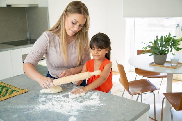 肯定的なママと娘が台所のテーブルで生地を練りに焦点を当てた。少女と母親が一緒にパンやケーキを焼きます。ミディアムショット。家族の料理のコンセプト