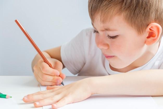 Сосредоточенный дошкольник рисует карандашом