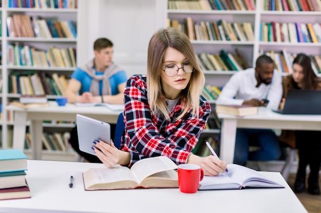 Сфокусированная довольно кавказская студентка сидя в месте coworking изучая с книгой и таблеткой, делая примечания и подготавливая к испытанию или экзамену в библиотеке
