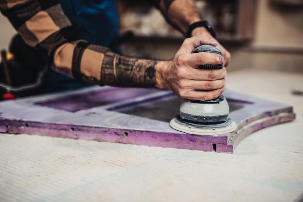 Сосредоточенный профессиональный плотник, работающий в своей мастерской, концепция деревообработки и мастерства.