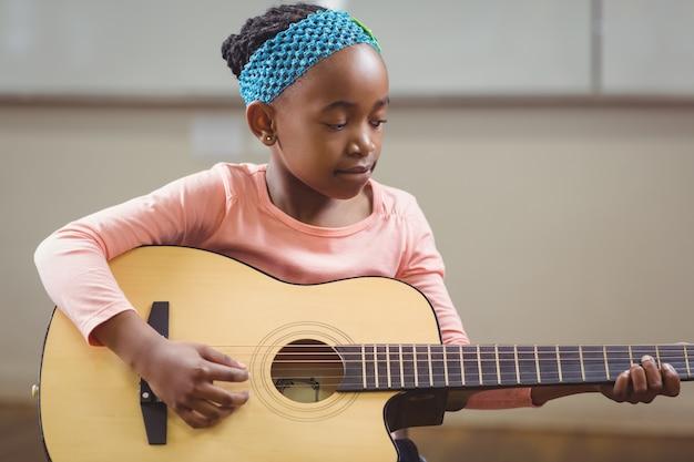 フォーカスされた瞳孔は、教室でギターを演奏