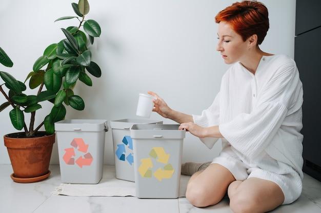Сосредоточенная рыжеволосая женщина сидит на ногах, сортируя мусор между небольшими мусорными баками у себя дома. на них нанесены стрелки разного цвета. держа пластиковый стаканчик.