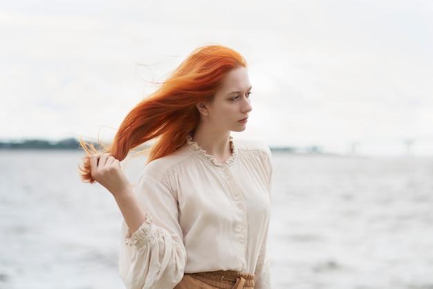 Focused redhead female looking away on riverside