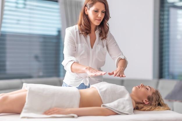건강 스파 센터에서 젊고 아름다운 여성과 치료 세션을 하는 집중된 레이키 치료사.