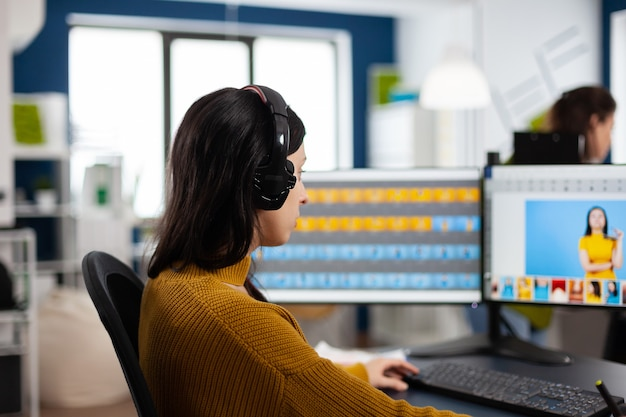헤드셋을 착용한 창의적인 사무실 환경에서 컴퓨터에서 작업하는 집중 보정 전문가