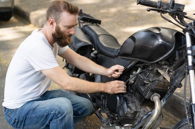 Сосредоточенный наездник, пытающийся реанимировать сломанный мотоцикл