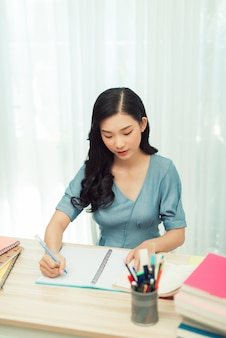 Focused school girl studying with books preparing for test exam writing essay doing homework at home