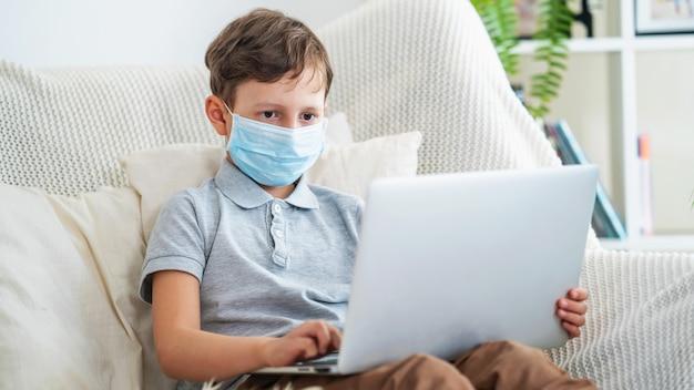 防護マスクに焦点を当てた少年は、ラップトップでソファーに座っています。