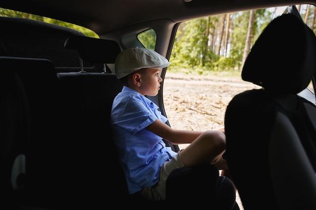 車の開いたドアの後部座席に座って森を見ている集中した男子生徒