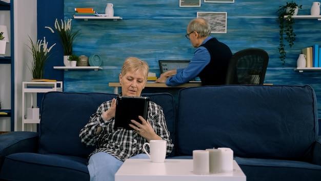 ソファに座ってリラックスした集中シニア祖母タイピングタブレットブラウジング検索情報sh ...