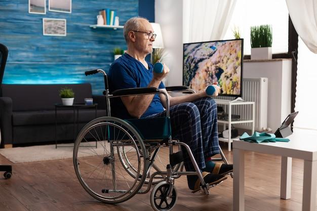 아령을 사용하여 팔 근육을 작동하는 거실에서 태블릿 컴퓨터에서 온라인 운동 비디오를 보고 있는 휠체어에 집중된 노인. 마비 후 신체 저항을 회복하는 무효 연금 수급자