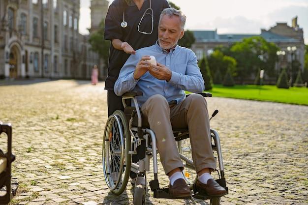 一緒に歩いている看護師のアドバイスを聞いてクリーム瓶を保持している患者を回復する焦点を当てた年配の男性