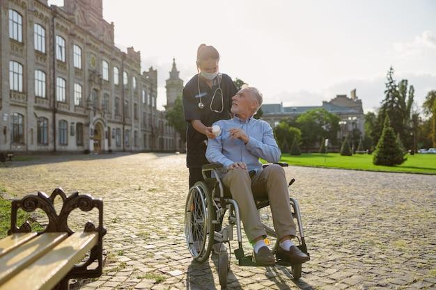 近くの屋外で一緒に歩いている看護師のアドバイスを聞いて患者を回復する集中した年配の男性