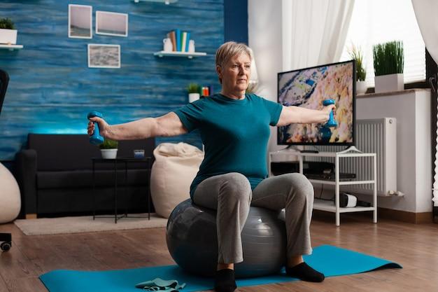 居間でスイスのボールに座っているフィットネスダンベルを使用して体の筋肉で働く腕を伸ばす焦点を絞った年配の女性。健康トレーニング中に筋肉のヘルスケアを行使する白人男性