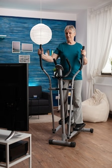 Focused senior woman working at legs muscle resistance cycling bicycle machine in living room during...