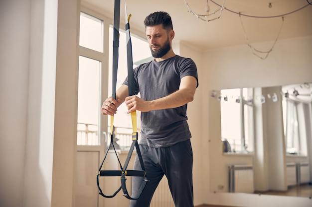 Сосредоточенный серьезный бородатый темноволосый молодой спортсмен-мужчина регулирует ремни перед тренировкой с подвешиванием