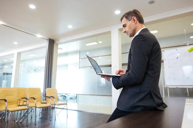 Сосредоточенный серьезный бизнесмен готовится к презентации, используя ноутбук в пустом конференц-зале