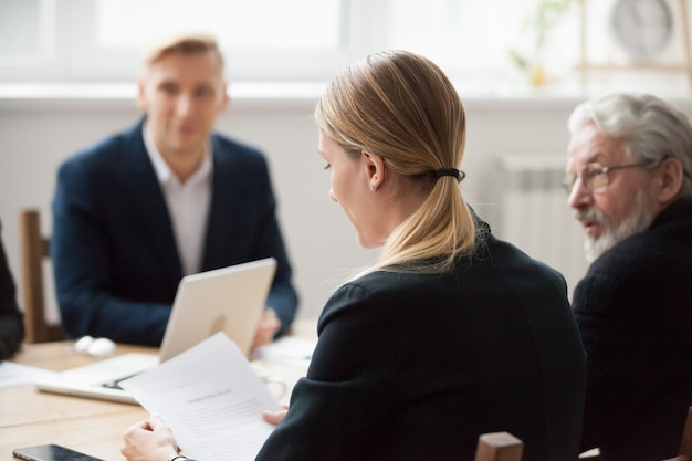 Focused serious businesswoman reading document at group meeting or negotiations