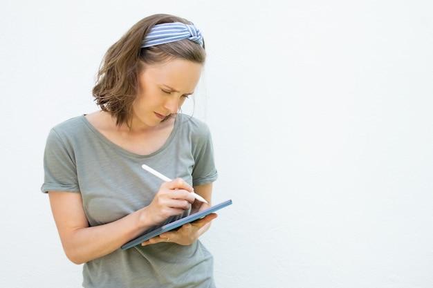 Сосредоточенный серьезный фрилансер, пишущий на экране планшета