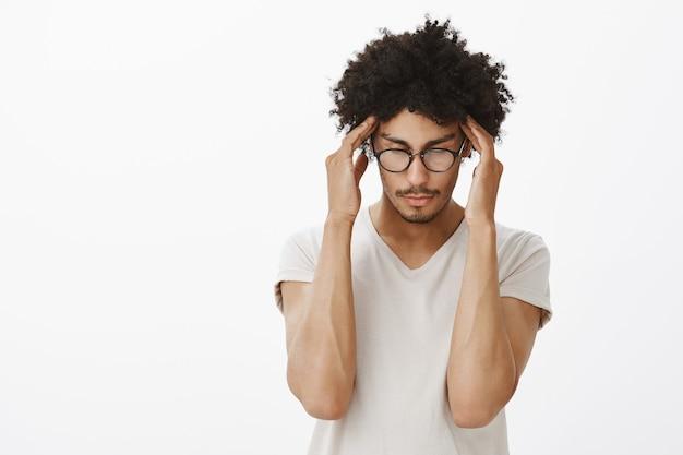 Сосредоточенный, серьезный темнокожий мужчина, мозговой штурм студентов, потирание висков, пытаясь сконцентрироваться
