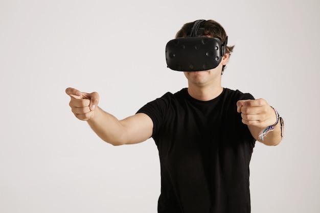 Сосредоточенный серьезный молодой геймер в черной футболке и очках виртуальной реальности протягивает руки, словно за рулем, изолирован на белом