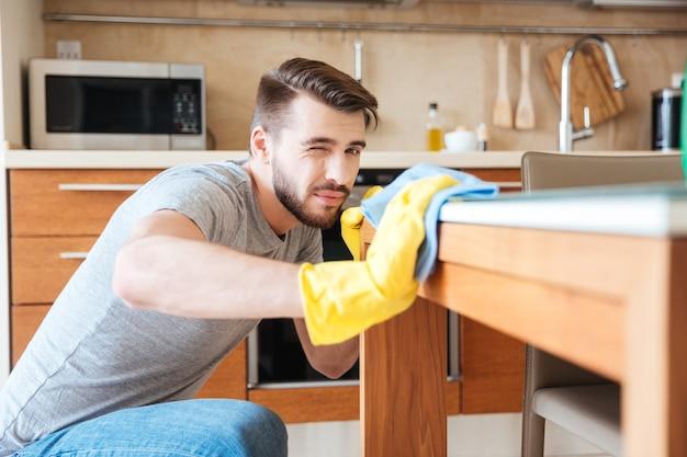 Сосредоточенный серьезный молодой человек чистит стол тряпкой на кухне
