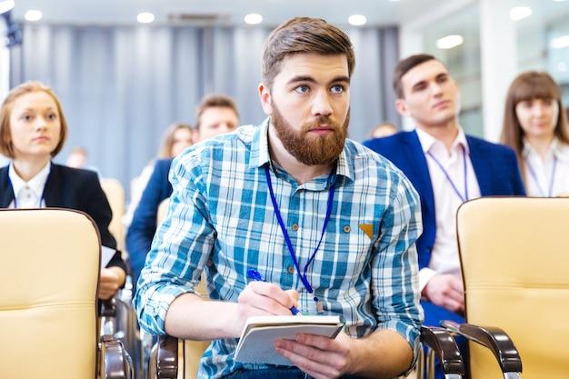 Сосредоточенный серьезный молодой человек слушает и делает заметки о презентации в конференц-зале