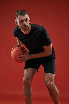 Сосредоточенный серьезно спортсмен в тренировке черной спортивной одежды изолирован на красном фоне