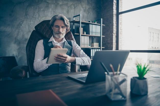 사무실에서 노트북에 집중된 숙련 된 사업가 쓰기 계획