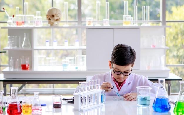 현대 실험실에서 화학을 공부하는 동안 실험실 코트와 안경을 쓴 똑똑한 아시아 학생에 집중했습니다.