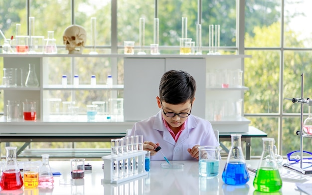 Focused smart asian schoolboy in lab coat and glasses examining samples while studying chemistry in modern laboratory.
