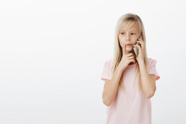 夕食に何を注文すればよいかを考えて、母親に電話をかけることに集中した賢い娘。思いやりのある若い女の子に集中し、意思決定を行い、スマートフォンで話し、人差し指を口の近くに持っている