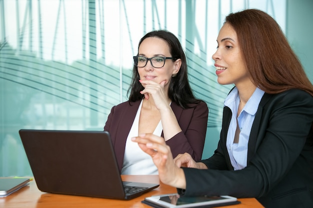 Focused smiling businesswomen looking at open laptop display