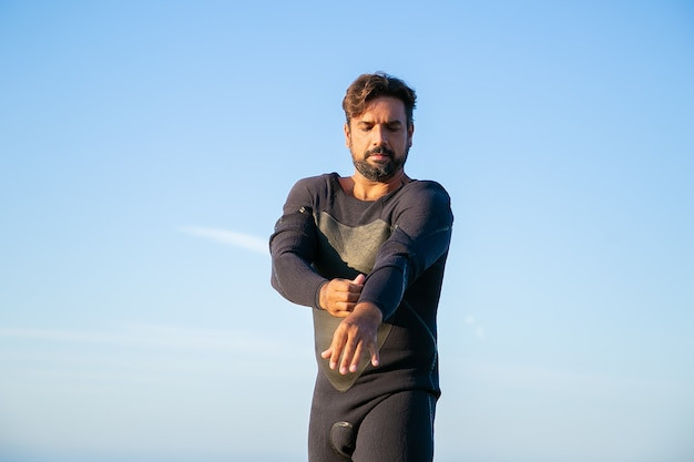 オーシャンビーチでサーフィンするためにウェットスーツを着ている集中スポーツマン
