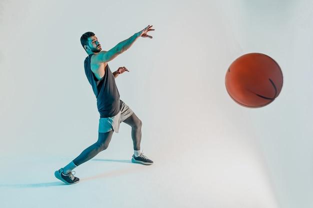 集中スポーツマンはバスケットボールのボールを投げます。若いひげを生やしたヨーロッパのバスケットボール選手。ターコイズブルーの背景に分離。スタジオ撮影