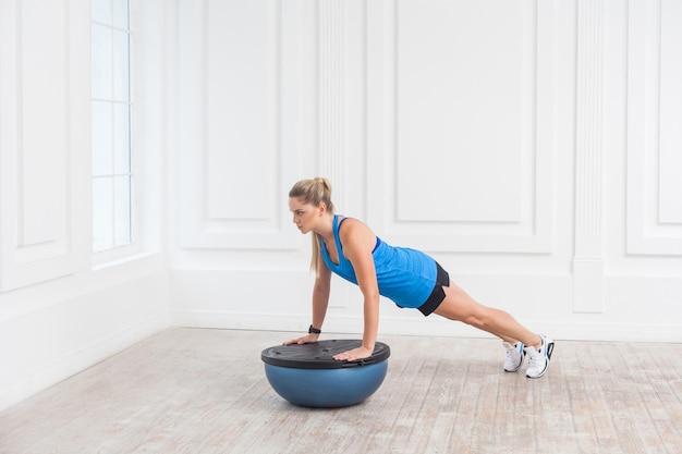 Сосредоточенная спортивная красивая молодая атлетичная блондинка в черных шортах и синем топе работает в тренажерном зале, делает планку для мышц живота на тренере по балансу босу, удерживая баланс на фитнес-мяче, в помещении