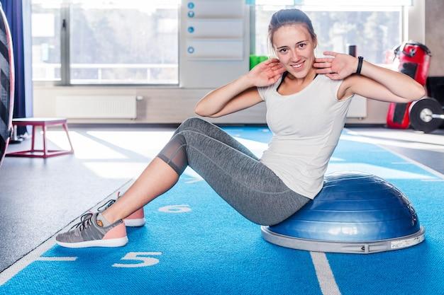 Сосредоточенная спортивная красивая молодая атлетичная брюнетка женщина в серых леггинсах и белой футболке работает в тренажерном зале, делая упражнения для мышц живота на тренажере баланса босу, ложится на фитнес-мяч в помещении