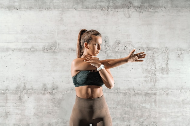 Сосредоточенная спортивная брюнетка с хвостиком и в спортивной одежде протягивает руку перед тренировкой перед серой деревенской стеной.