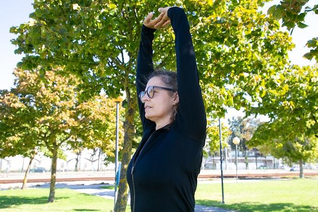 体を伸ばし、手を上げ、公園で運動しながら目をそらしている、焦点を絞ったスポーティな中年女性。幸福またはアクティブなライフスタイルの概念