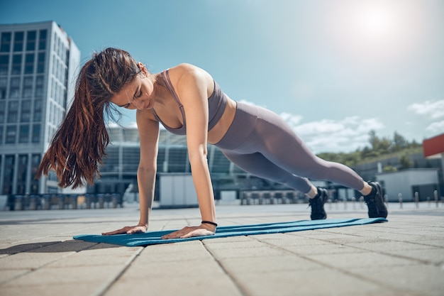 外のヨガマットで高い板の運動をしている焦点を絞ったスポーティな強い若い女性