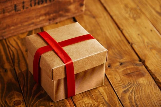 Сфокусированная квадратная картонная коробка закрыта и обернута красной шелковой лентой на деревенском деревянном столе рядом с винтажным ящиком