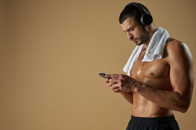 Focused strong athlete in black sportswear with towel on his shoulder standing in studio with