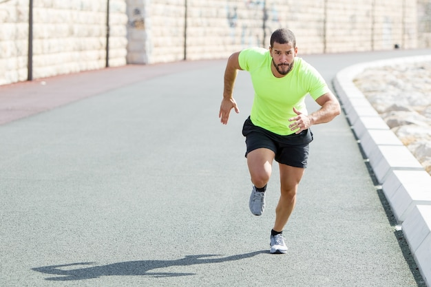 Focused strong sporty man running fast on road
